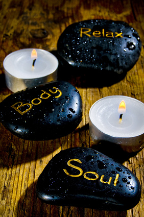 wellness and reiki concep with three black massage stones with words soul, body, relax and drops of water over wood background